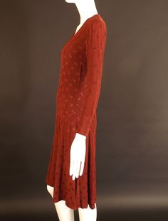 Adorable 1920s dress in a burgundy silk brocade. Dropped waistline with a flirty twirl skirt. Condition: Scattered pin holes through out. One pea size hole on the back skirt.