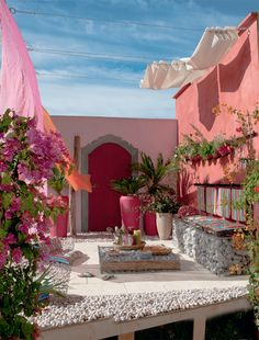 warm pinks corals in Mexican patio space. upholstered bench in striped fabric
