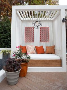 An oversized daybed, accented with flowing white curtains and pops of orange, transforms a sleek white pergola into a serene and private spot to catch a few z's next to a backyard deck.