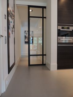 Warmgrijze gietvloer. PRachtige combinatie met zwarte frame glasdeuren. We kunnen een sleuf maken voor schuifdeuren. Vraag vrijblijvend een offerte aan via www.designgietvloer.nl