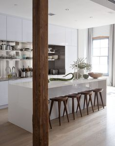 This 'urban cabin' kitchen has glossy white cabinetry, stainless steel countertops and backsplash, open shelving, wooden backless stools, floor to ceiling gray drapes and an unfinished wood column.
