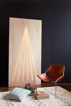 This super modern tree alternative was simply made by drilling holes in a piece of ply wood and poking LED Fairy Lights through them - Christmas Tree Decorating Ideas (houseandgarden.co.uk)