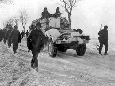 """A column of U.S. troops from the 9th Armored Division (""""Phantom""""), an armored car of the headquarters company of the 9th Engineer Battalion, 9th or artillery battalion, moving on winter road. Time taken: 1945 Location: Western Europe"""