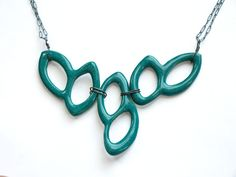 """Adorn yourself with this garland-like necklace. Three pieces of hand cut porcelain are wired wrapped and ready to go anywhere. Total necklace dimensions are 8""""w x 1.5""""h. Strung on antique bronze chain, though shown on oxidized sterling.This necklace is back in stock temporarily! Get it while you can!!!"""