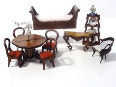 Half Scale Dollhouse Miniatures - An incredibly small chair with hand-carved decoration and a fancy console table, both by Susanne Russo. Also a sleigh bed by Jeanne Chapman, a whatnot filled with decorated china by Debbie McKnight and a set of four balloon-back chairs with upholstered seats with a pedestal table with two removable leaves, signed but not recognized.