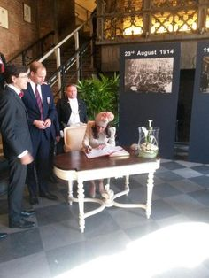 After the Liège events morning William and Kate were joined by Prince Harry, and the threesome traveled to Mons, Belgium. They then attended a reception with dignitaries and families whose relatives fought in World War I. Below you see Kate signing the gu