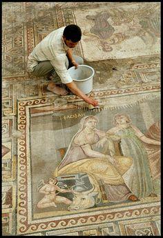 Détail de la mosaïque de Pasiphaé. Cette mosaïque exceptionnelle d'environ 80 m² recouvrait le sol d'une grande salle de réception. Elle constitue l'une des découverte majeure du dernier demi-siècle. Il y est question du mythe de la reine Pasiphaé (sur son trône), désirant se cacher dans une vache de bois construite par Dédale et son fils Icare (à droite, avec les outils de menuisier) pour aller séduire le taureau dont elle est amoureuse. En haut à droite, le palais du célèbre Labyrinthe…