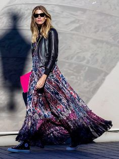 Veronika Heilbrunner wears a printed maxi dress, leather jacket, and high-top sneakers