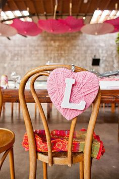 chair backs. heart shaped chair backing. wedding decoration. pink. Love the up-side-down parasoles in the background!