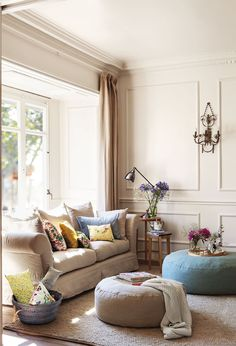 Pequeño salón con dos pufs de distintos tamaños y sofá con cojines de diferentes colores junto a la ventana_ 00368642