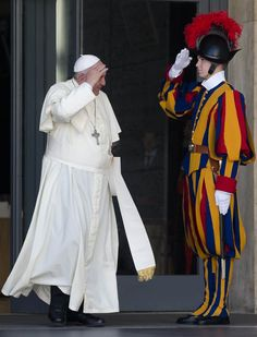 A Vatican Swiss Guard salutes Pope Francis holding his skull-cap as he leaves after the morning session of a two-week synod on family issues at the Vatican, Monday, Oct. 6, 2014. Francis has urged bishops to speak their minds about contentious issues like contraception, gays, marriage and divorce at the start of the meeting aimed at making the church's teaching on family matters relevant to today's Catholics. (AP Photo/Alessandra Tarantino)
