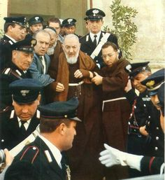 Practically the only time Padre Pio left his monastery was at election time when he went to vote. In this photo, Padre Pio is being escorted from a voting station to a waiting car which was showered with flowers as it passed through the town. Hundreds would line up on the streets to wave to him as he passed by. He encouraged everyone to vote, stating that it is the duty of all Christians.