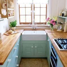 Wood counter-tops on teal furniture nestled between white walls.