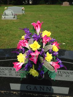 Silk cemetery middle tomb vase using pink lilies, yellow roses, purple filler with white and gold mesh ribbon. May 2015