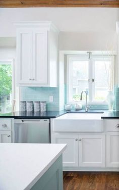 Tiffany blue kitchen features white cabinets adorned with nickel cup pulls paired with black quartz countertops and a tiffany blue subway tiled backsplash. A farmhouse sink next to a stainless steel dishwasher. White Kitchen Backsplash, Kitchen Redo, Kitchen Tiles, Kitchen Colors, New Kitchen, Kitchen Remodel, Backsplash Ideas, Kitchen Cabinets, Blue Cabinets