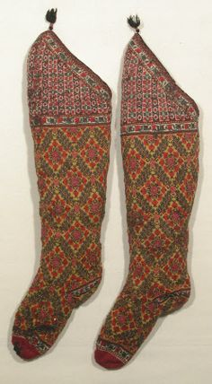 One of a pair of knitted wool socks from Persia. The toe is claret, the main part is lemon yellow ground with blue/black/shades of red. The knee has a cream ground with black/reds/green. They are lined with knitted wool. There is a narrow edging of interwoven silk in pink and black with silk cored silver thread with a black tassle. Similar to a pair in Indianapolis Museum of Art 16.1117 aandb. (male)