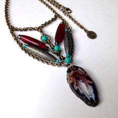 GET SERIOUS ABOUT DESIGN! Feel inspired and bold with the red and black Druzy agate slice with little crystals that have amazing light reflecting qualities. This is a modern tribal or Native American style agate pendant necklace with antique brass chain, turquoise and red bone horn tubes.