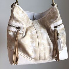 {COACH} Gold Tassel Hobo Purse Hobo style Coach bag. Good condition. Wear marks slightly visible (please refer to photos). Gold and cream colored with tassels at exterior zipped pockets. One zipped interior pocket and two open interior pockets. Please feel free to use the offer button. Coach Bags Hobos