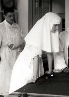 Tatiana in her nursing uniform with hospital patient in background