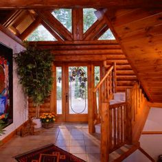 Foyer displays custom gable glass surrounded by white cedar log finishes