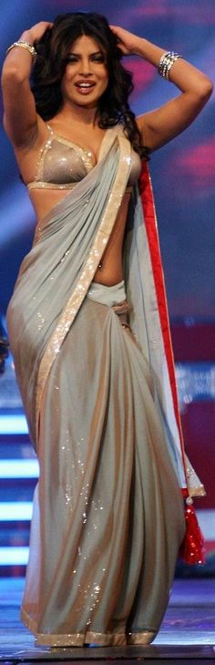 Curvy Priyanka dancing with gay abandon in a slinky saree and bikini bouse. Simply too hot for words!