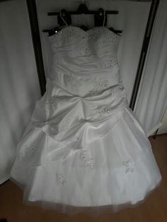 De draperie en het kant met de kraaltjes, van het lijfje en van de bovenste roklaag is aangepast.