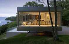 Raised horizontal house enclosed in glass with open interior | Modern House Designs