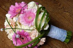 süsser Brautstrauss mit Gerbera in pink und rosa, kombiniert mit weissen und creme farbigen Rosen. Ein paar Perlen und mit Typha umwickelt