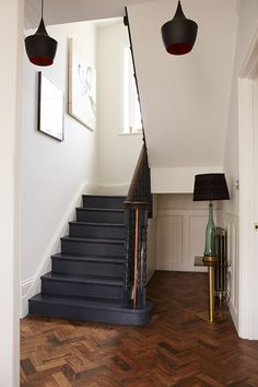 Entrance stairs. Tulipwood parquet floor from Architectural Forum. Tom Dixon Beat pendant lighting. Reclaimed enamel lamp shades. Vintage glass lamp with shade from Rockett St George.