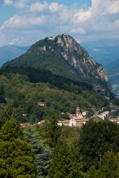 Ticino / Chiesa dei Santi Giorgio e Andrea (church) and houses below summit of Monte San Salvatore and high above Lago di Lugano (Lake Lugano) with Lugano town at foot of Monte Bre and Monte Boglia in back.