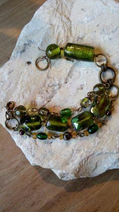 Bronzen armband gemaakt met diverse groene glaskralen, in drie rijen.