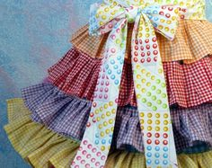 This is made to order, so please allow about a week for me to make it for you please- thanks! I made this cute candy-land style apron with some really cool fabrics; vintage and new ginghams in multi colors for the ruffles (gingham ruffle colors may vary), a cute confetti multi dot for the bib, and a candy-dot fabric for the ties. I made the cute cupcake applique with some really nice wool felt (cupcake colors may vary). The backing to the skirt is vintage gingham also. I was inspired by…