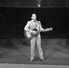 Johnny Cash American country and western singer Johnny Cash (1932 - 2003) plays guitar and sings on 'The Ed Sullivan Show,' New York, New York, February 8, 1959
