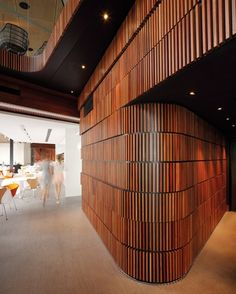 Faced with vertical timber battens, a curving wall forms a central spine.