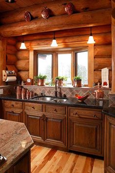 Log cabin kitchen. Love the short backsplash to the logs.