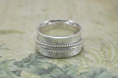 Diese schwere Walze gedruckt Sterling Silberring Spinner, manchmal auch als einen Meditation Ring, besteht aus 18 Gauge (1mm) dick Sterling Silber Blatt, das 1 cm breit ist. Es ist mit zwei verdrillten Draht Spinner und einem Runddraht Spinner gekrönt. Dieser Ring hat eine schöne Frosteffekt dazu die schön durch die glänzenden Spinner kontrastiert. Ringe wie diese werden oft als zappeln Ringe oder Schmuck zappeln, weil die Spinner beweglich ist.  Schauen Sie sich einige meiner anderen…