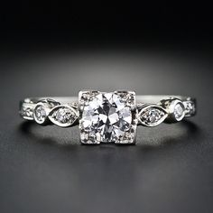 This 1930s-era vintage diamond engagement ring highlights a bright and shining European-cut diamond weighing .40 carat. The diamond sparkles from within a four-cornered setting with hand-engraved sides and a scooped gallery which has the effect of making the diamond appear larger than its actual weight. The elegantly shaped shoulders each twinkle with a pair of single-cut diamonds leading down to a hand-engraved ring shank. A sweet and lovely estate engagement ring.