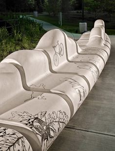 Around Town, Chapel Hill, NC. The seat back is a sculpted, undulating elevation that references the region's rolling topography. Engraved into the bench are images from the area, such as local architecture, wildlife, and sports references.