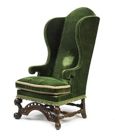 An impressive William & Mary oak and upholstered wing-back armchair, circa 1700 With high arched padded back, winged-shaped sides and squab-cushion upholstered in emerald-green velvet, the 'corner' horse-bone front legs joined by an arched and pierced fore-rail, with baluster turned H-form low stretcher and conforming rear stretcher,