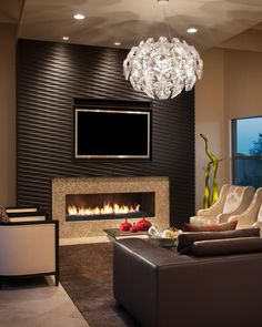 HGTV likes this modern, neutral living room with wood-clad accent wall, fireplace, tiled fireplace surround, recessed lighting, unique glass chandelier, neutral armchairs, brown leather sofa and contemporary rug.