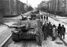 A small column of Soviet soldiers stand beside a Soviet ISU-122 tank during a brief lull in the Battle of Berlin. Berlin, Germany. May 1945.