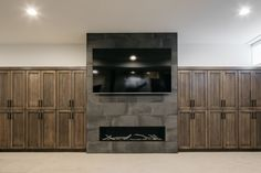 In the Basement a tile-faced fireplace is flanked by Maple cabinets with V-groove doors Talking about storage Cabinets are 91 x 84 on each side #basement #fireplace #cabinet