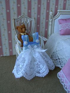 A pretty girls dress to display in your 1/12 scale dollhouse or shop. For display purposes only...it will not fit onto a doll. Made from a lovely, white, embroidered tulle and sweet blue ribbon.Trimmed with a white silk bow and white trims. These little display clothes add interest to a
