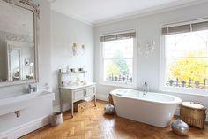 Salle de bain à la fois romantique et design... Luminaires classiques, parquet et grand miroir anciens, mais des équipements tendance. Alliance réussie.