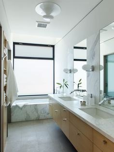 This modern bathroom features a floating light wood vanity with a stone counter and dual undermount sinks. A frosted window provides privacy while you're in the bath, but at the same time lets the light in to the room.