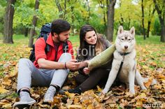 young caucasian couple hiking with siberian husky dog. Hikers with map and…