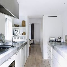 In this narrow kitchen, the all white colour scheme maximises the space and light.