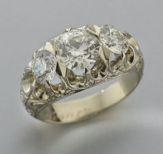 Gents 18K gold and diamond three stone ring featuring a central old European cut diamond, 2.02 cts.