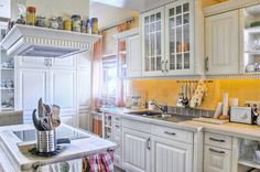 A charming country kitchen that leans towards a cottage-style feel. The detailing on the cabinetry, combined with the light butcher block countertops, makes for a charming smaller kitchen. Open shelving on the lower cabinets displays the glassware and small decorative china bowls. A small ledge around the vent hood is used to store dried spices and herbs.