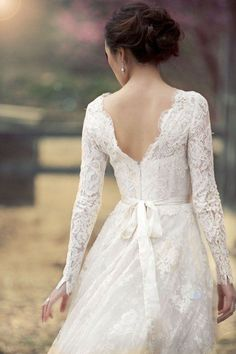 Pretty pose for a bride whose dress has lovely details in the back.